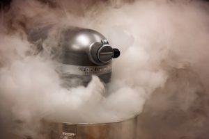 """Beispielbild für den Abschnitt """"Was kann eine Küchenmaschine?"""". Zu sehen ist eine Küchenmaschine von KitchenAid, umnebelt von Rauch"""